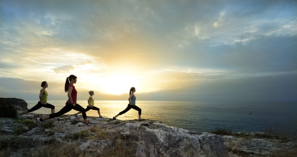 4 Frauen auf einem Felsen in einer Yoga Pose im Hintergrund der Sonnenuntergang im Meer