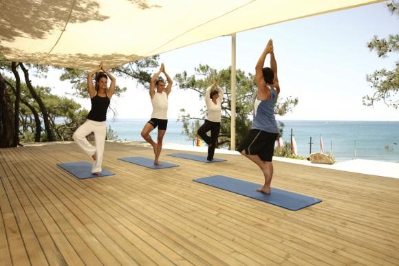 Yogalehrer und 3 Yogaschüler beim Praktizieren von Yoga mit Blick auf das Meer