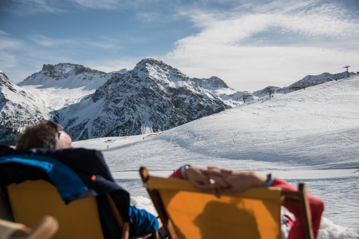 Entspannte Momente im Liegestuhl des Bergrestaurants mit Blick auf die sonnige Skipiste