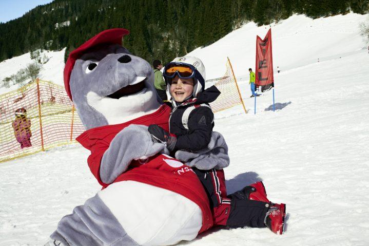 Kind im Schnee mit Maskottchen ROBY