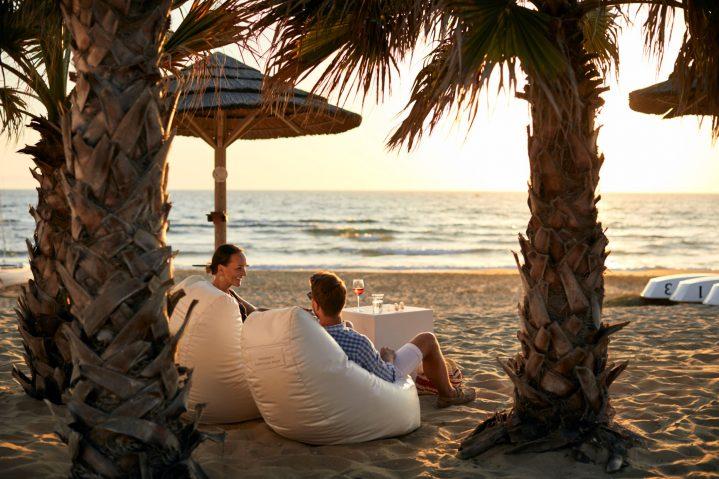 Paar am Strand beim Sonnenuntergang in Sitzsäcken im ROBINSON Kyllini Beach, Griechenland