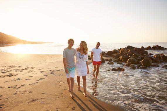 Familie beim Strandspaziergang bei Sonnenuntergang am ROBINSON Club Daidalos