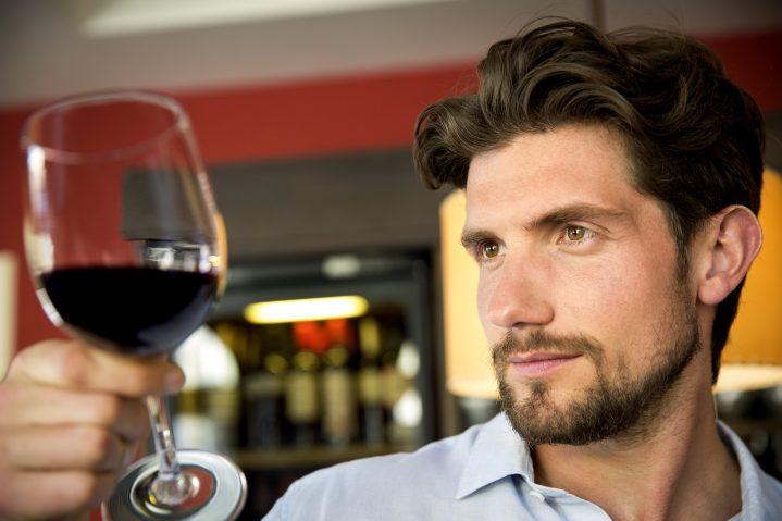 Mann begutachtet ein Glas Rotwein