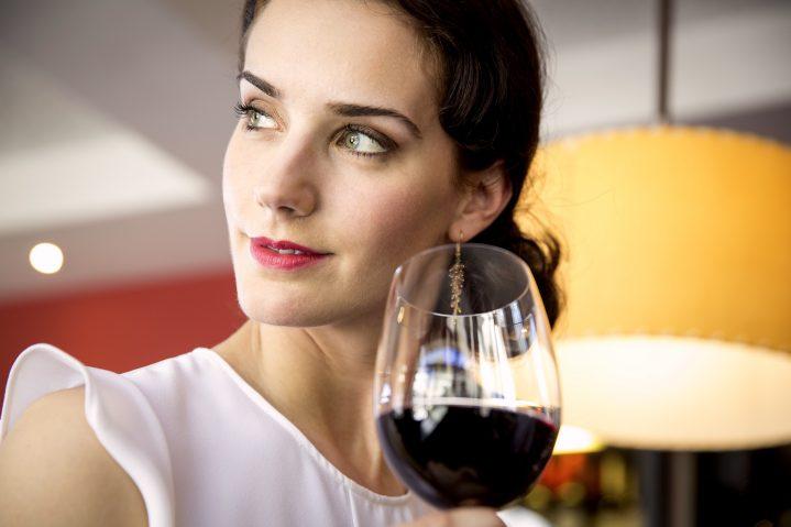 Frau mit einem Glas Rotwein in der Hand