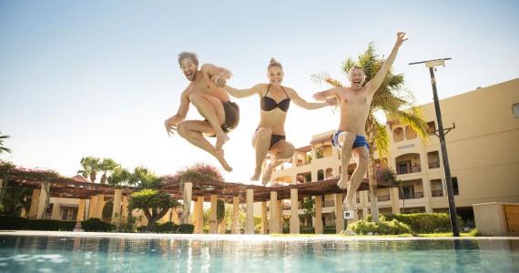 Drei Leute springen zusammen in einen Pool