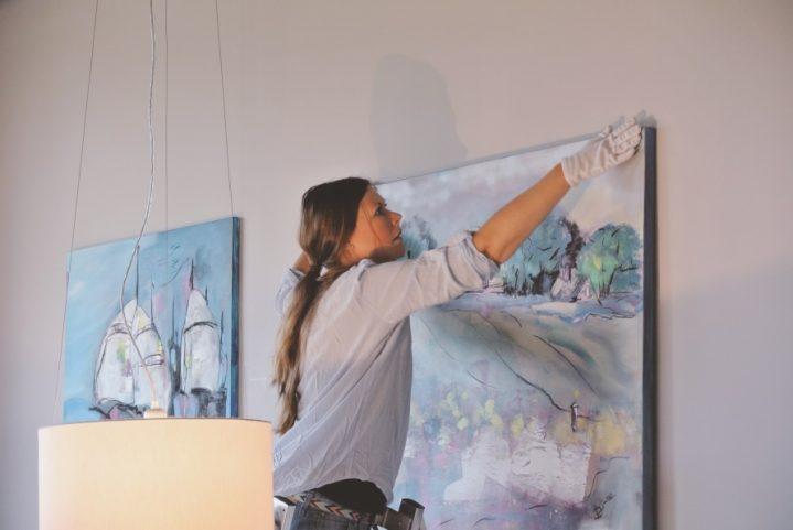 Künstlerin hängt Bilder an die Wand bei ROBINSON