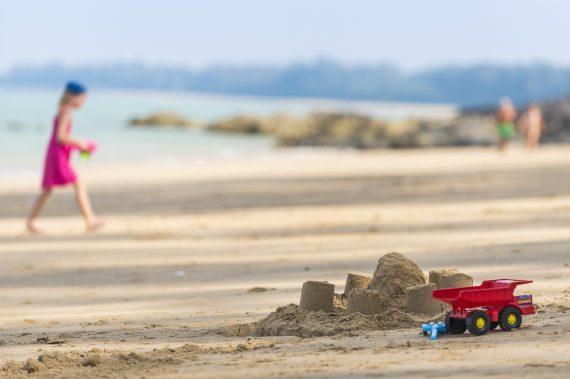 Kind und Kinderspielzeug am Sandstrand