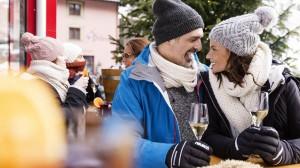 Ein Pärchen sitzt in Winterbekleidung draußen auf einer Terrasse und trinkt Sekt
