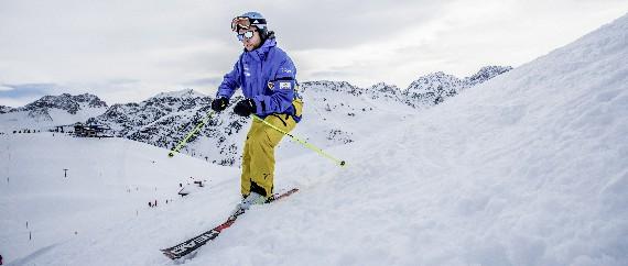 Mann auf einer Skipiste mit warmer Skikleidung,Helm und Sonnenbrille