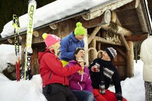 Vier Freunde sitzen auf der Terrasse einer Skihütte und trinken etwas Warmes