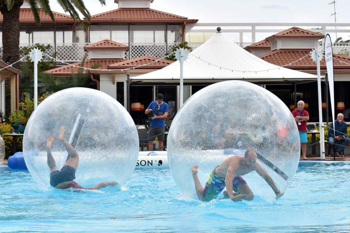 Sportler bei einer Challenge in Wasserbällen auf dem Wasser