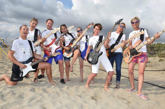 Sportler mit Gitarren am Strand
