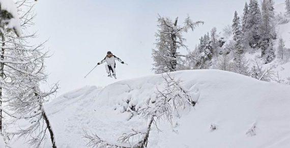 Mann fährt fernab der Pisten rasant ski.