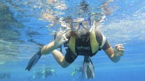 """Frau mit Schnorchel unter Wasser, die das handzeichen für """"Alles ist gut!"""" gibt"""