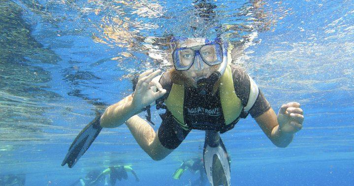 Frau mit Schnorchel unter Wasser, die das handzeichen für