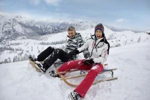 Zwei Erwachsene sitzen auf einem Schlitten rodeln voller Spaß