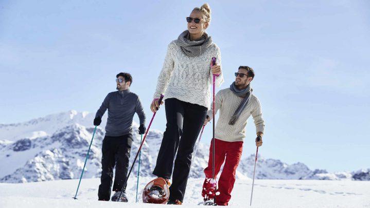 Drei Personen laufen mit Schneeschuhe durch den Schnee
