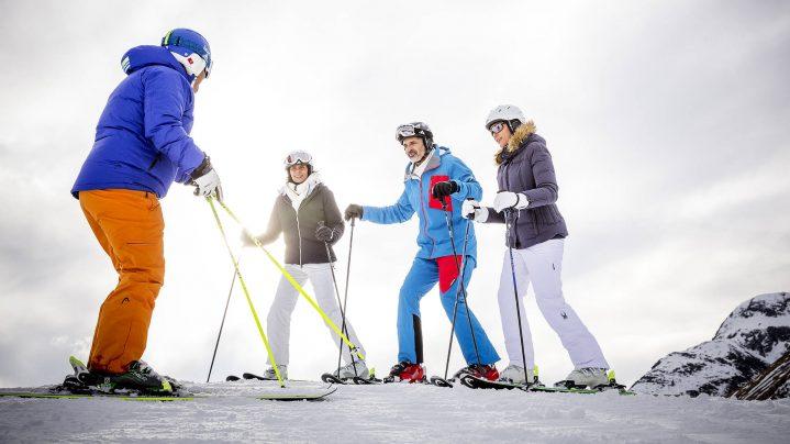 Drei Erwachsene stehen auf Skiern und ihr Skilehrer erklärt Ihnen Techniken