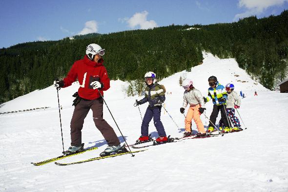 Skilehrer fährt auf Skiern und seine Schüler fahren ihm hinterher