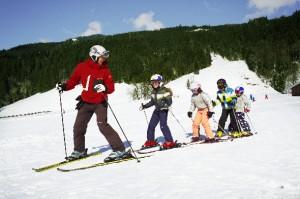 Skilehrer fährt Ski und seine Schüler folgen ihm