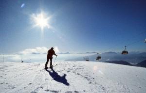 Mann fährt ski und die Sonne strahlt kräftig auf die Piste