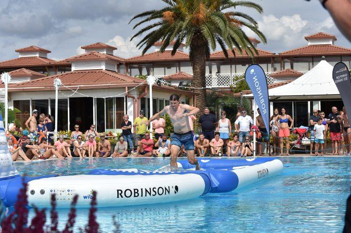 Sportler läuft über einen Hindernisparcours im Wasser