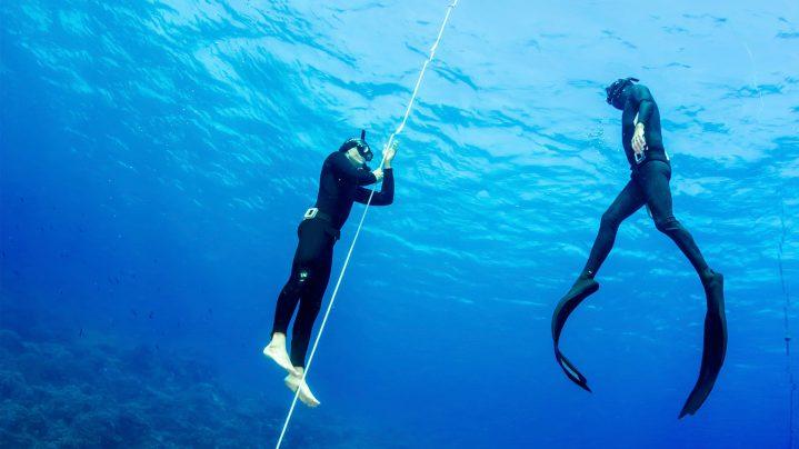 Tauchlehrer von ROBINSON bringt einem Gast an der Schnur unter Wasser in kleinen Schritten das Tauchen bei
