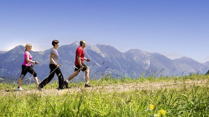 Drei Erwachsene laufen mit Stöcken einen Wanderweg entlang