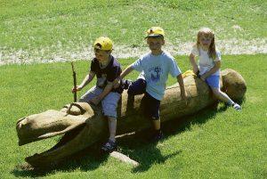 Drei Kindern sitzen auf einem großen Holzstamm