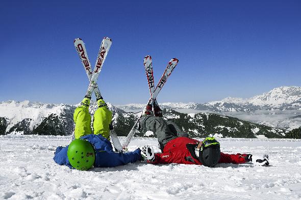 Zwei Personen liegen in Skikleidung im Schnee und halten ihre Füße, mit den Skiern daran, in die Luft