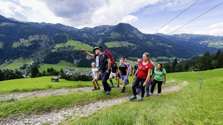 Gruppe von Erwachsenen und Kindern wandern einen Berg hinauf