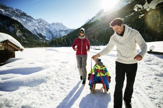 Familie beim Schlittenfahren im Schnee