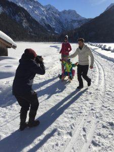 Fotograf fotografiert Familie mit Schlitten im Schnee