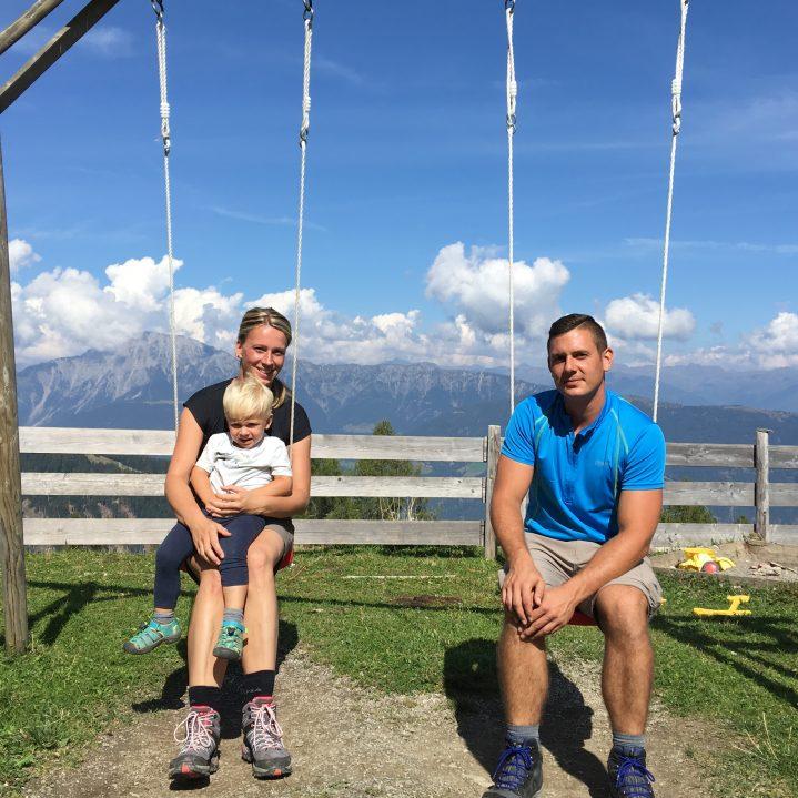 Eltern mit Kind auf Schaukel in den Bergen