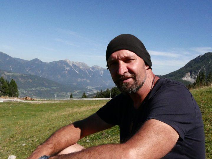Mann auf Almwiese in den Bergen