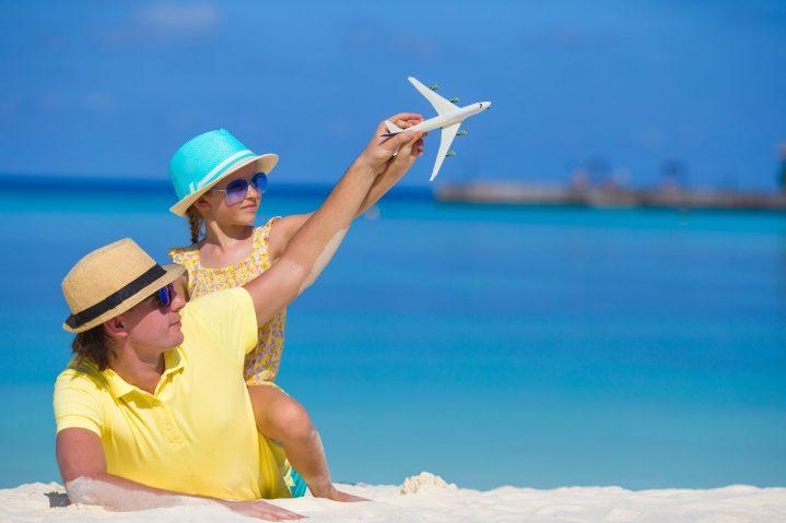 Vater und Tochter am Strand mit Spielzeugflugzeug nachhaltiger Urlaub