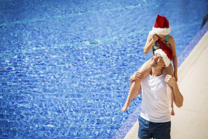 Vater und Tochter mit Weihnachtsmütze am Pool