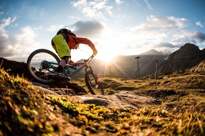 Mountainbiker beim Downhill fahren im Sonnenuntergang in Österreich
