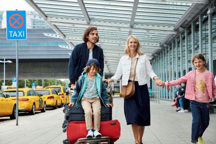 Familie mit Gepäcktrolley vor dem Flughafengebäude