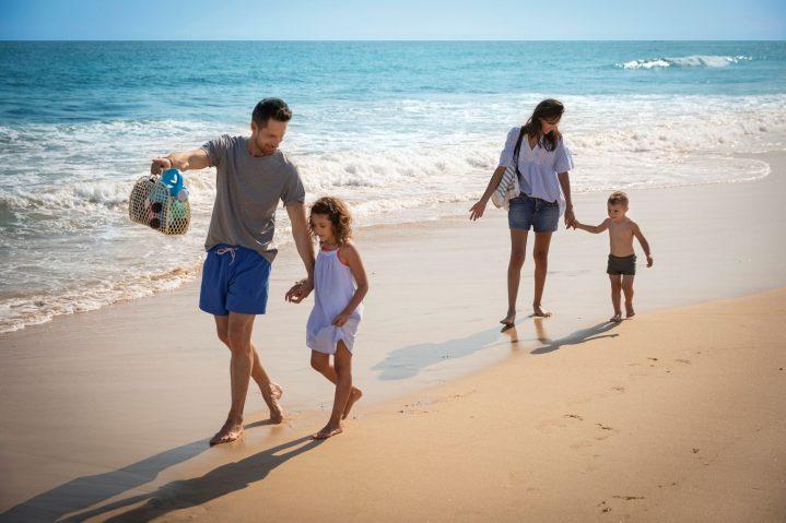 Mutter, Vater und 2 Kinder gehen am Strand spazieren