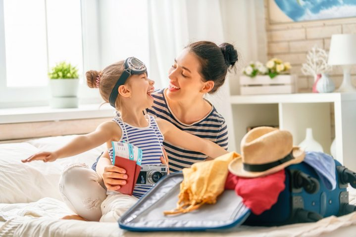 Mutter und kleines Kind sitzen vor einem geöffneten Reisekoffer und haben Spaß