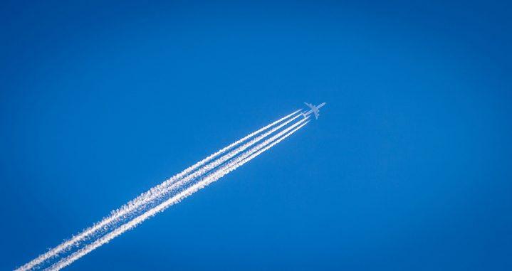 Flugzeug mit Kondenzstreifen am wolkenlosen Himmel Photo by William Hook on Unsplash