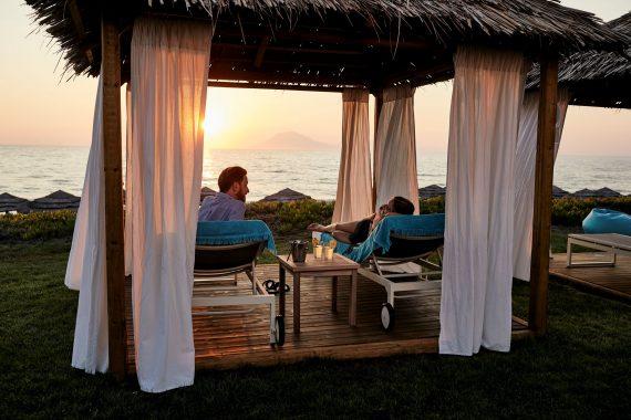 Pärchen auf Daybed bei Sonnenuntergang im ROBINSON Club Kyllini Beach, Peloponnes, Griechenland