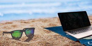 Laptop und Sonnenbrille am Strand