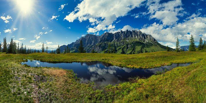 Ausblick auf Landschaft mit einem See im Vordergrund.