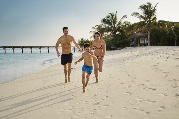 Eltern mit Kind laufen den Strand entlang