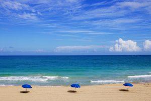 Ein einsamer Strand mit blauen Sonnenschirmen.