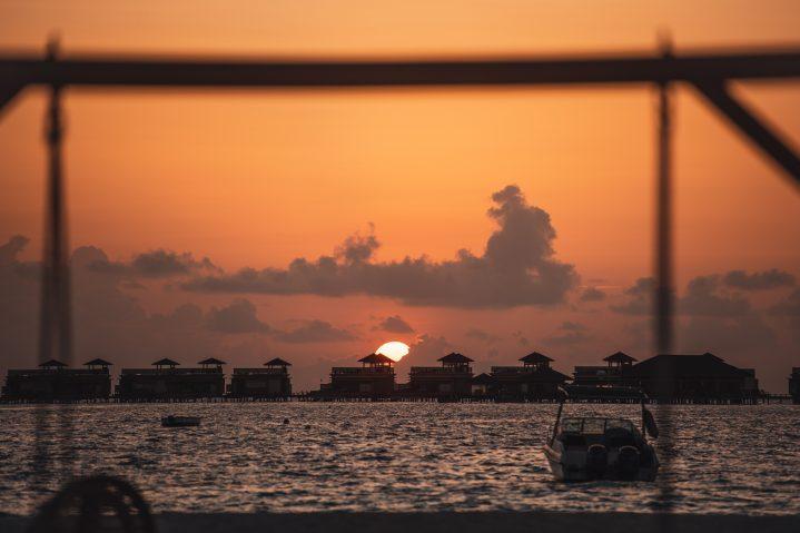 Speedboat vor Wassernbungalows bei Sonnenuntergang